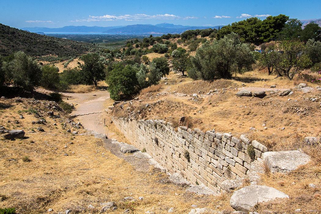 Blick oberhalb des Grab der Klytaimnestra auf den Dromosweg. Am Horizont schimmert blau die Ägäis mit der weiten Bucht von Argos.
