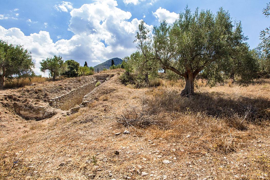 Links im Bild ist der Dromos und die Abschlußmauer vom Grab der Genien zu sehen. Wer an dieser Stelle ein paar Meter nach rechts weitergeht kommt direkt zum Kyklopen-Grab.