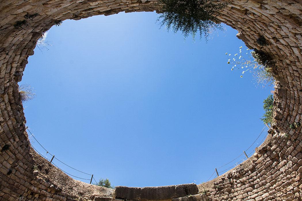 Die inzwischen eingestürzte Kuppel wirkt heute wie ein Auge in den blauen Himmel über Mykene.