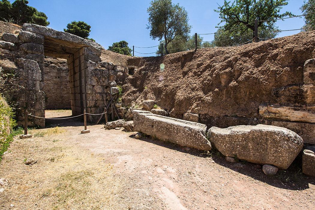 Mycenae argolis lions grave tholos peleoponnes greece Das Löwengrab (1450 v. Chr.) liegt direkt unter dem Burgberg und dem Archäologischen Museum. Dromos und Fassade bestehen aus geglätteten Steinen, die Kuppel ist eingestürzt.