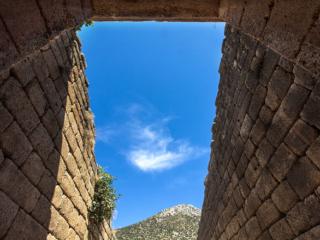 Blick auf dem Torgang hinauf zum Berggipfel und in den tiefblauen Himmel.