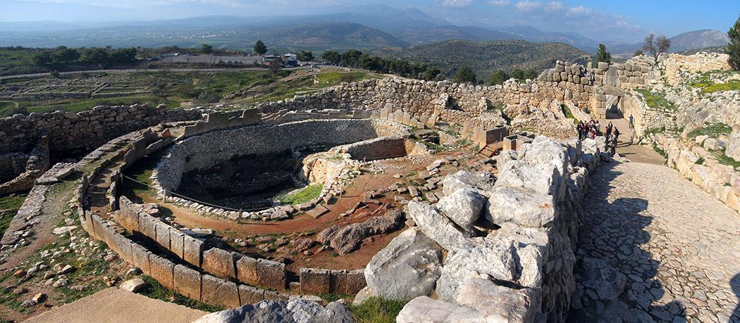 Mycenae citadel grave circle a argolis peloponnes greece wikipedia Andreas Trepte Blick von der Aufstiegsrampe auf das Gräberrund A. Am Ende der Rampe ist deutlich die Rückseite des Löwentors erkennbar. Foto: Wikipedia, Andreas Trepte
