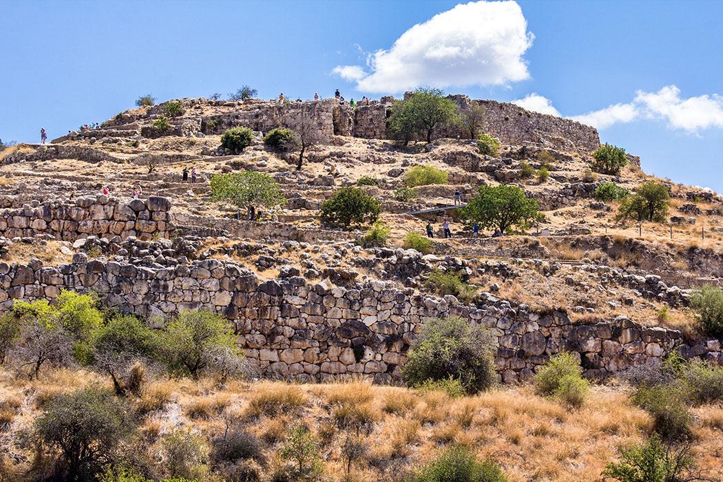 Mycenae citadel title argolis peloponnes greece Mykene: Blick auf die bronzezeitliche Zitadelle mit ihren wuchtigen Mauern. Die Besucher winden sich wie Ameisen hinauf zum Gipfel mit den Resten des königlichen Thronsaales.