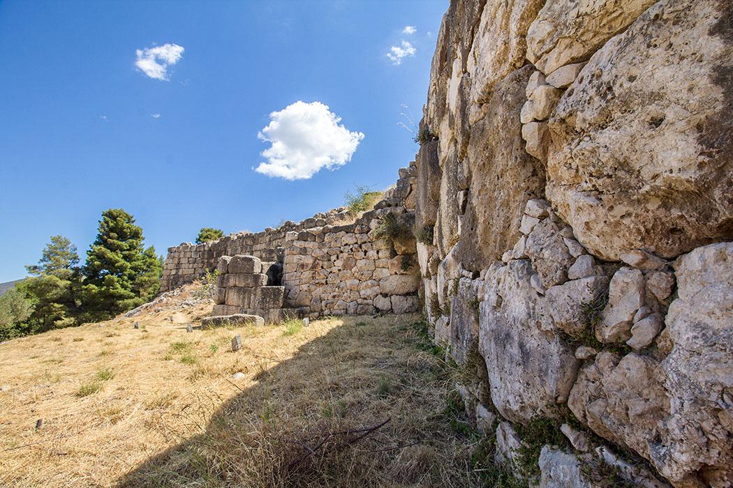 Mycenae cyclopean walls 01 argolis peloponnes greece - reise-zikaden.de - Der Blick entlang der Mauer zurück zum Löwentor. Direkt vor uns imposantes Polygonalmauerwerk. Gut erkennbar ist das Quadermauerwerk vom einstigen Wachturm (Mitte).