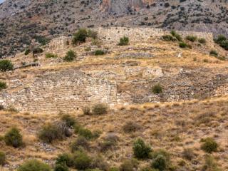 Blick von der Unterstadt hinauf zur Burg. Gut erkennbar der etwa zwölf Meter hohe Mauerabschnitt. Am Gipfel die Terrassierungen des Megaron und der Köngigsgemächer.