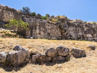 In der Mitte des Fotos ist gut das einstige Fundament eines Wachturms vor dem Löwentor erkennbar. Durch die Mauern verdeckt liegt der Eingang zur Burg. Im weiteren Mauerverlauf sind deutlich Polygonalmauerwerk und Quadermauerwerk erkennbar.