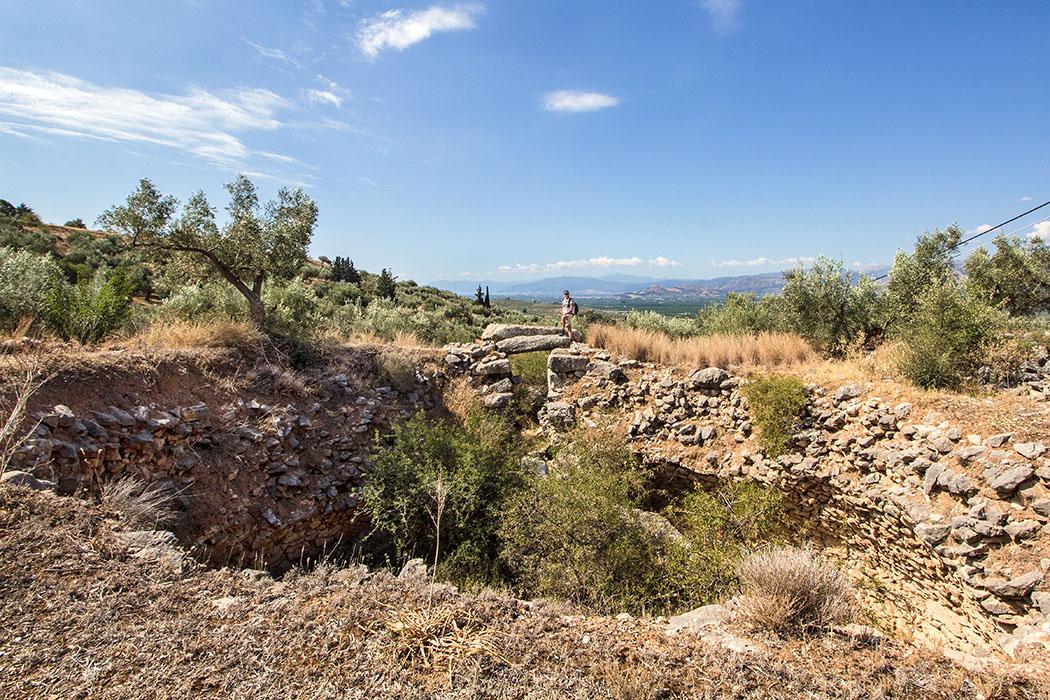 Mycenae epano phournos tholos tomb panagitsa hill argolis peloponnes greece Das Grab von Epano Phournos zählt mit dem Kyklopengrab zu den beiden ältesten Gräbern Mykenes. Hans steht auf einem der Torsteine über dem Eingang in das Grabrund mit elf Metern Durchmesser.