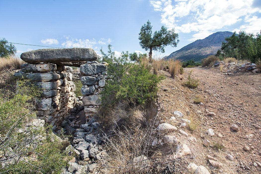 Das Grab von Epano Phournos liegt direkt neben dem Feldweg, der auf den Panagitsa-Hügel hinaufführt. Das Portal hat eine Höhe von etwa 4,60 Meter, unten eine Breite von 2 Meter und verjüngt sich nach oben auf 1,60 Meter.