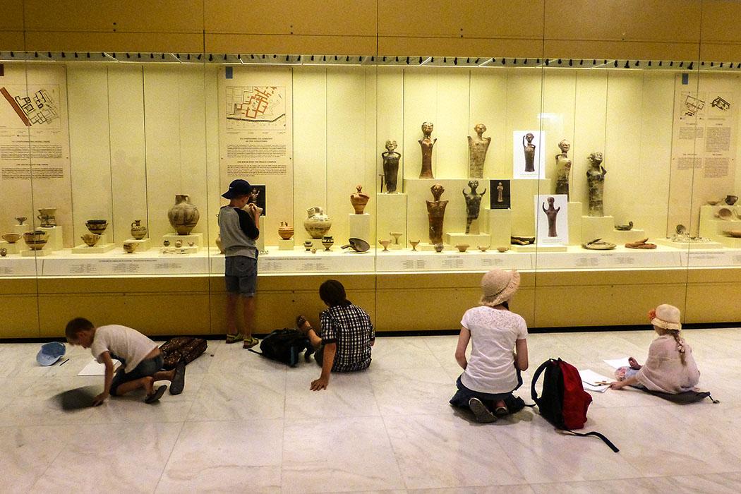 Eifrige Schüler im Archäologischen Museum von Mykene zeichnen Vasen und Statuen in ihre Arbeitshefte.