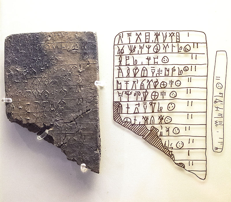 Schwarz verbrannte Tontafel mit Linear B-Schrift. Interessant ist, dass auch die Schmalseite beschriftet wurde, ähnlich wie neuzeitliche Buchrücken. Die Tontafeln wurden damals nur getrocknet, erst durch den Brand im Palast wurden die Täfelchen konserviert.