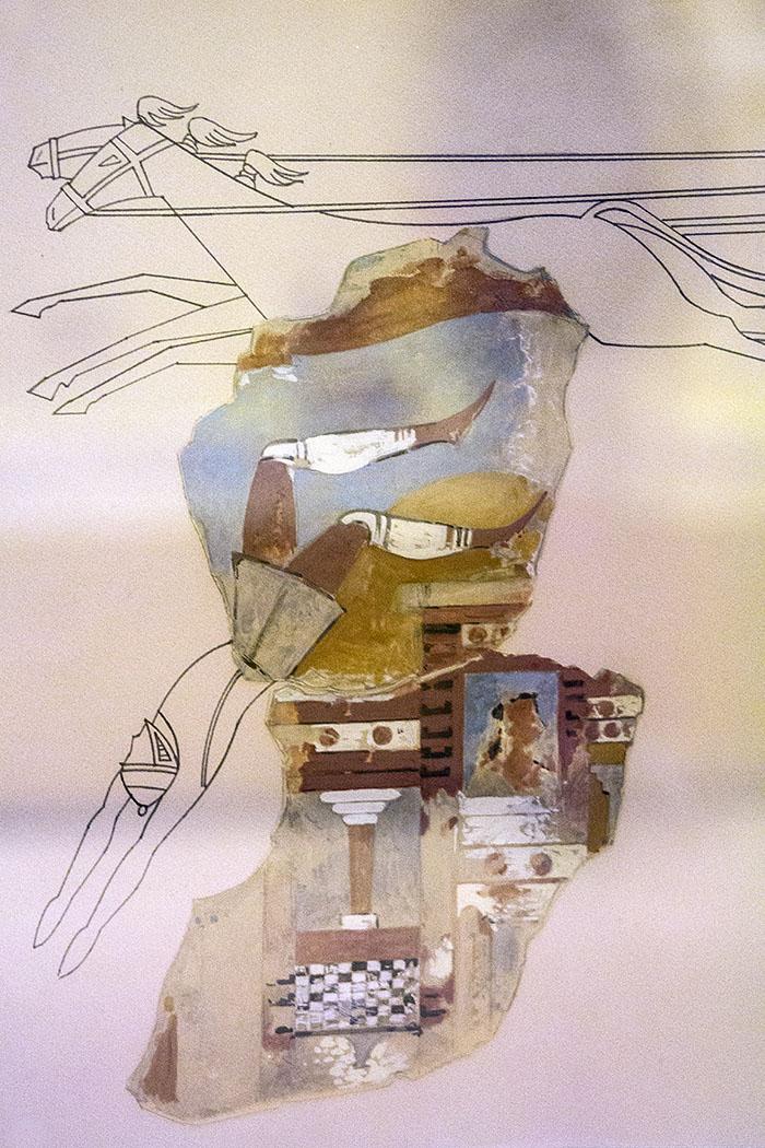Das Fresko zeigt eine Kampfszene: Ein Streitwagen bringt einen Krieger zu Fall, im Hintergrund ist der Palast mit Säulen und Fenstern zu sehen. Eine Person blickt aus dem Fenster auf das Kriegsgeschehen.