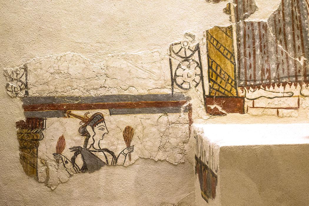 Das Freskodetail zeigt eine Frauenfigur in einem mykenischen Kleid mit Weizenbüscheln in den Händen. Hinter ihr ist eine Säule sichtbar, vor der Figur eine Tür mit Rosettenverziehung. Datierung 1250 bis 1180 v. Chr.