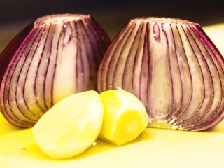 Zwiebel ebenfalls in feine Würfel schneiden, Knoblauch durchpressen und zum Hackfleisch geben.