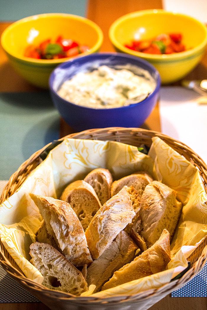 Der Tisch ist bereits fertig gedeckt. Tomatensalat, Tzatziki und Weißbrot warten auf die Bifteki.