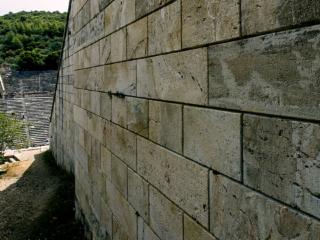 An den Außenmauern des Theaters von Epidaurus beeindruckt die exakten Steinmetzarbeiten der Antike.