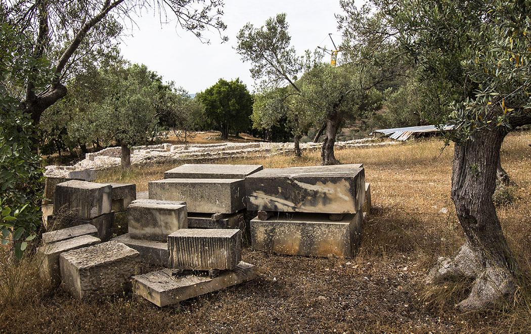 Ein Blick über den Zaun zeigt Mauerreste von großen Gebäuden. Die Steinquader im Vordergrund sind wohl für den Wiederaufbau gedacht.