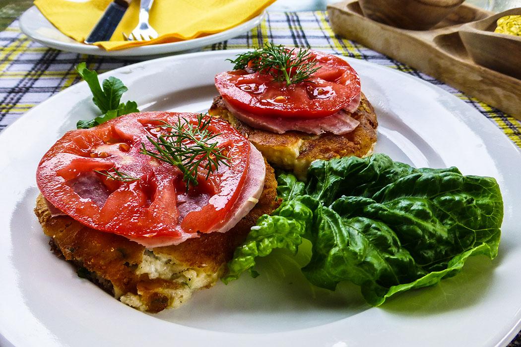 Dann folgen kleine knusprige Käse-Taler mit Tomatenscheiben.