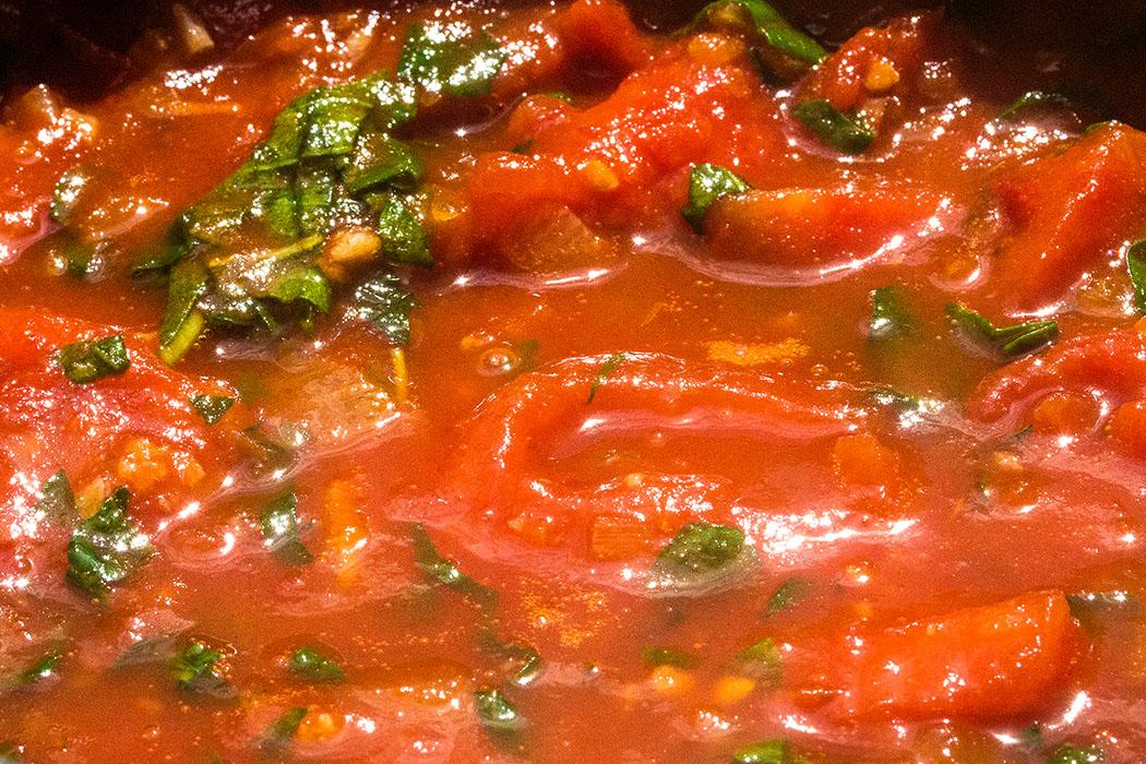 Wenn die Tomatensauce zu einem süßlich duftenden Konzentrat eingekocht ist, salzen und pfeffern, einen Spritzer Essig zugeben.