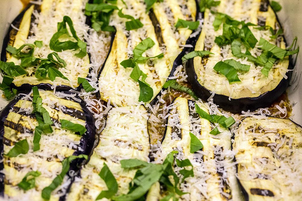 In einer Gratinform etwas Tomatensauce verteilen. Darauf streuen Sie etwas Parmesan, gefolgt von einer Lage gegrillter Auberginenscheiben.