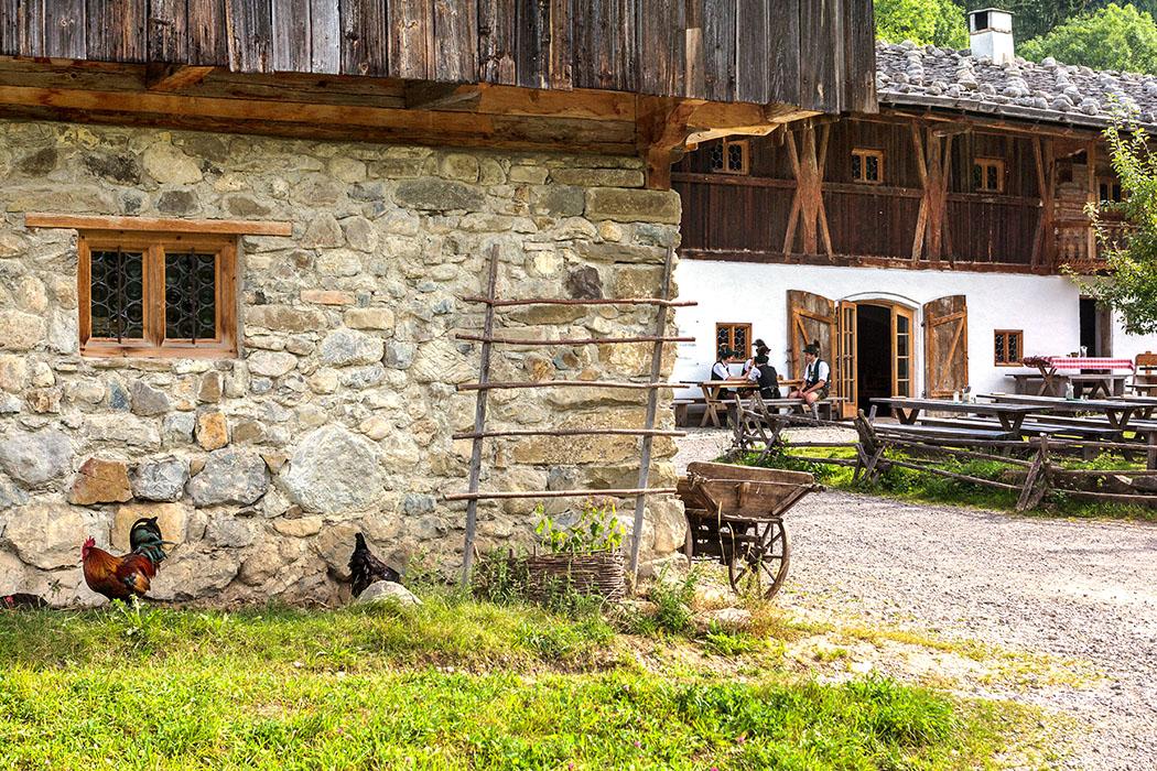 """Blick vom Behamhof hinüber zum Wirthaus """"Wofen"""", die ersten Gäste sitzen bereits im Biergarten."""