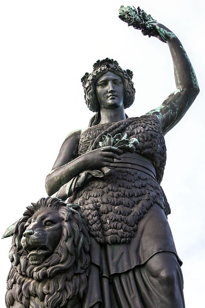 statue bavaria ruhmeshalle theresienwiese muenchen munich germany Die Bavaria - Symbolgestalt und Patronin Bayerns. Bekleidet ist sie mit Tunika und Bärenfell, die rechte Hand umfasst das Schwert. Mit dem linken Arm streckt sie einen Siegeskranz in die Höhe, der den Berühmtheiten in der Ruhmeshalle gilt. Neben ihr sitzt schützend ein Löwe, das Wappentier der Wittelsbacher, er symbolisiert Mut und Unerschrockenheit.