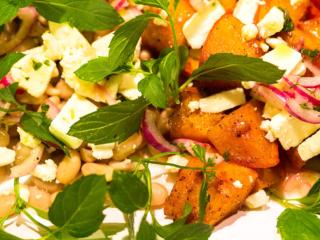 Lauwarmer Kürbis-Salat mit weißen Bohnen, roten Zwiebeln und einem Zitronen-Minze-Dressing.