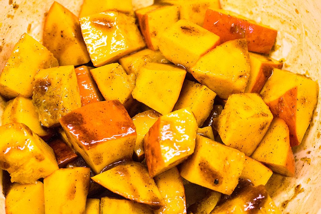 Kürbiswürfel mit Olivenöl, Zimt, Honig, Salz und Pfeffer vermischen und für 10 Minuten abgedeckt marinieren lassen.