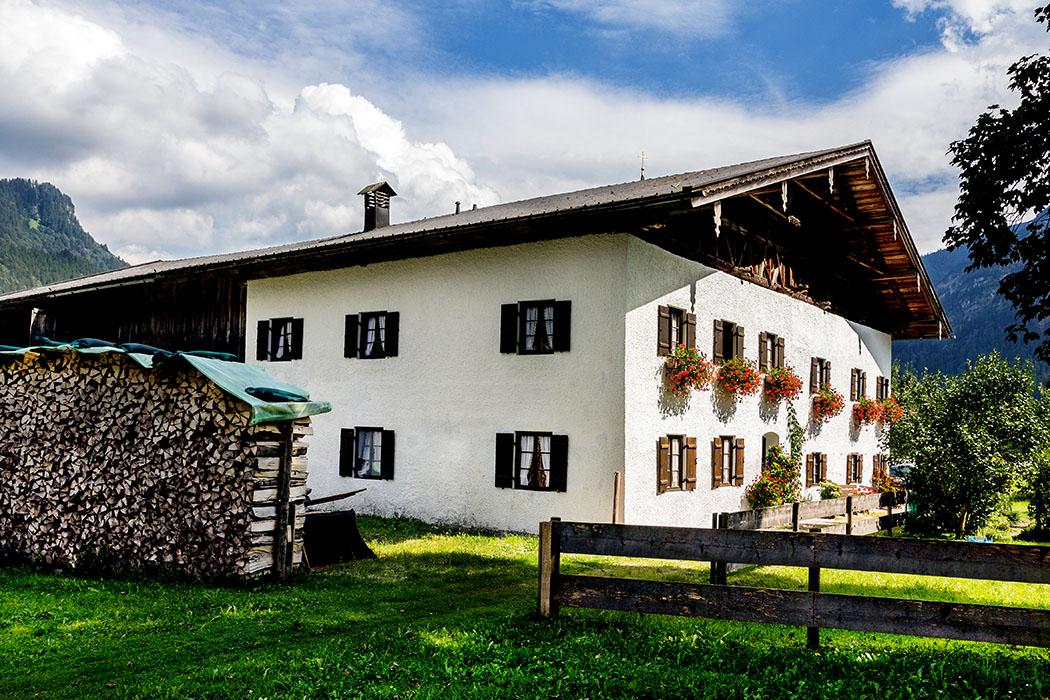 Einhof in Graswang, zweigeschossiger Flachsatteldachbau mit Kniestock, Zierbund und Traufbundwerk von 1786.