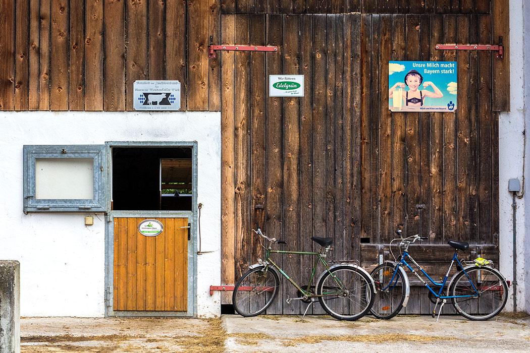 Moderner Stalleingang in Graswang mit zwei Fahrrädern älteren Baujahrs.