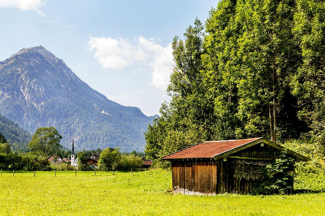 Das Dorf Graswang mit seinem spitzen Kirchturm kommt in Sicht.