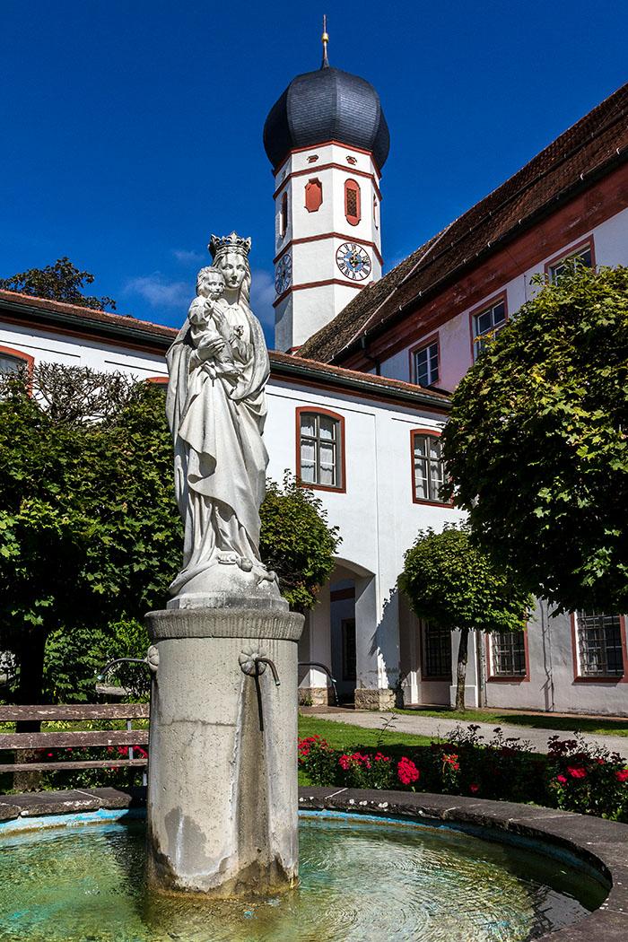 Der Marienbrunnen im Vorhof mit dem Turm der Stiftskirche Peter und Paul.