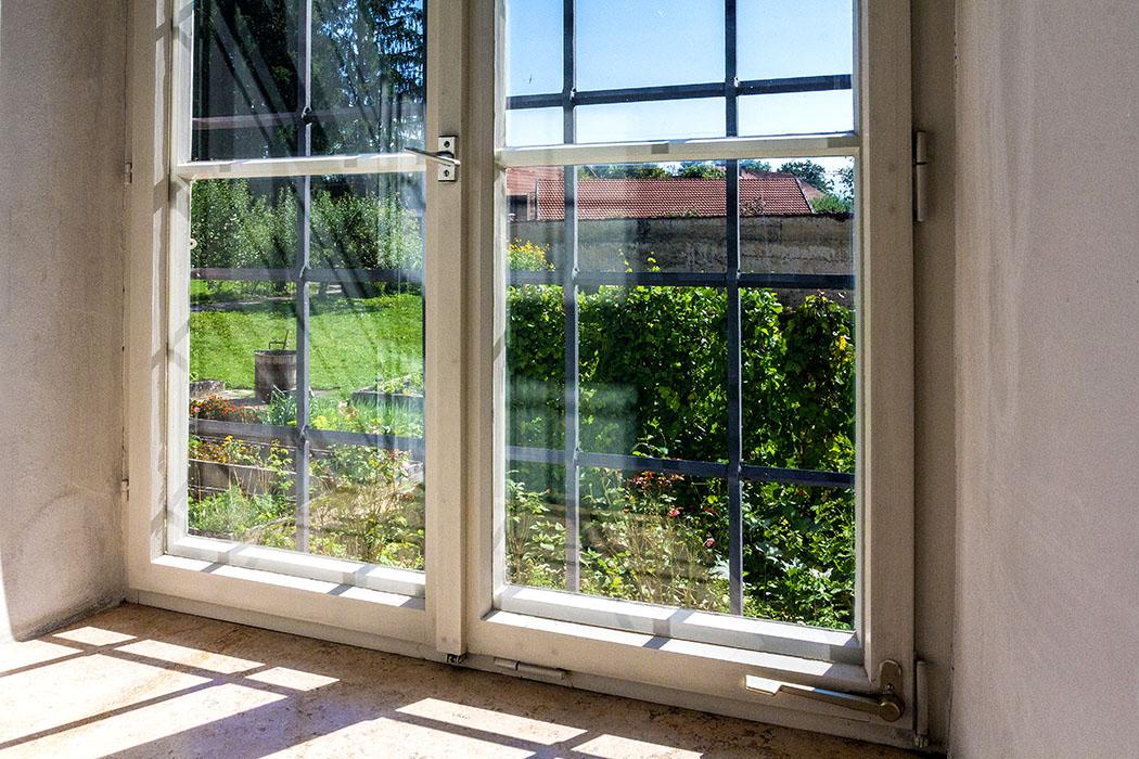 Blick durch ein Fenster in den Klostergarten.