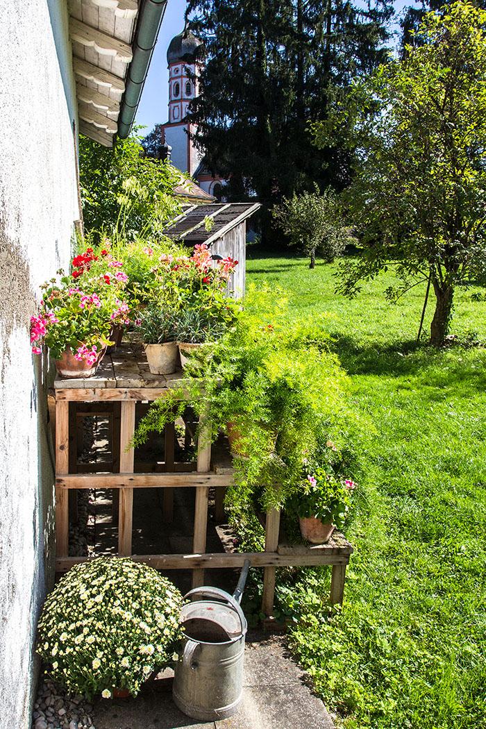 Eine einfache Etagere beim Gärtnerhaus im Klostergarten, im Hintergrund die Marienkirche von Beuerberg.