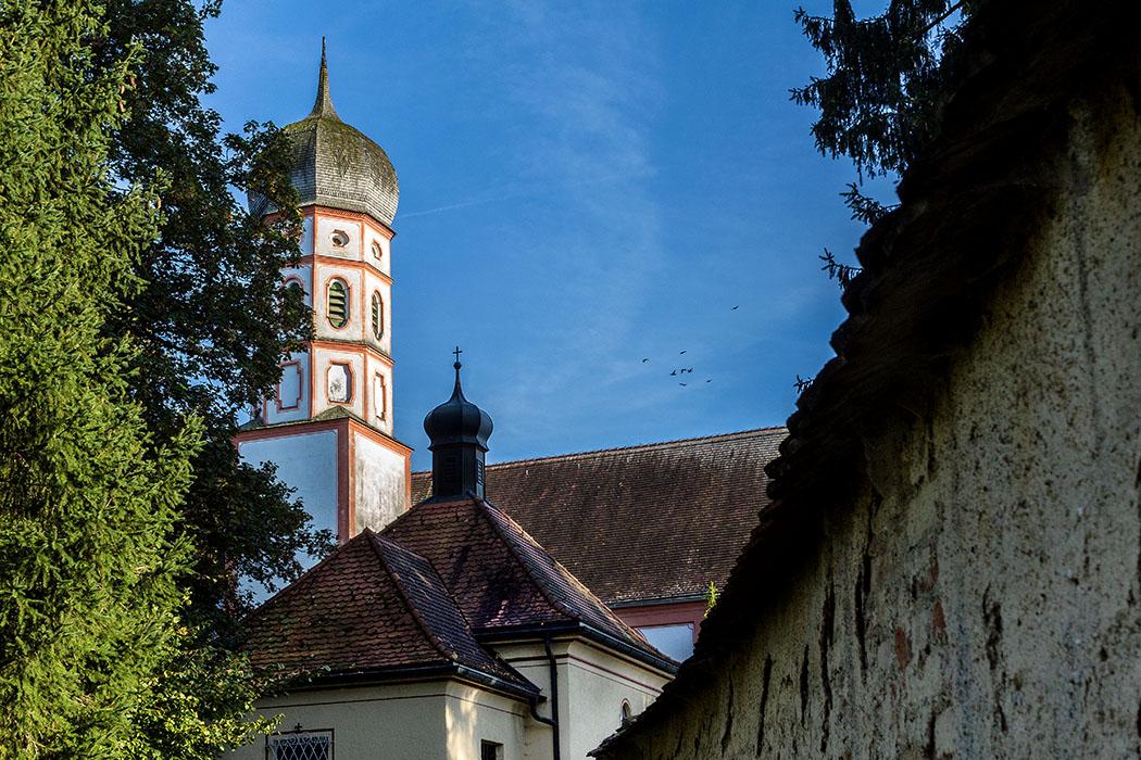 Das Abendlicht senkt sich über Kloster Beuerberg und der Marienkirche. Ein schmaler Fußweg führt an den Klostermauern entlang hinunter zur Loisach.