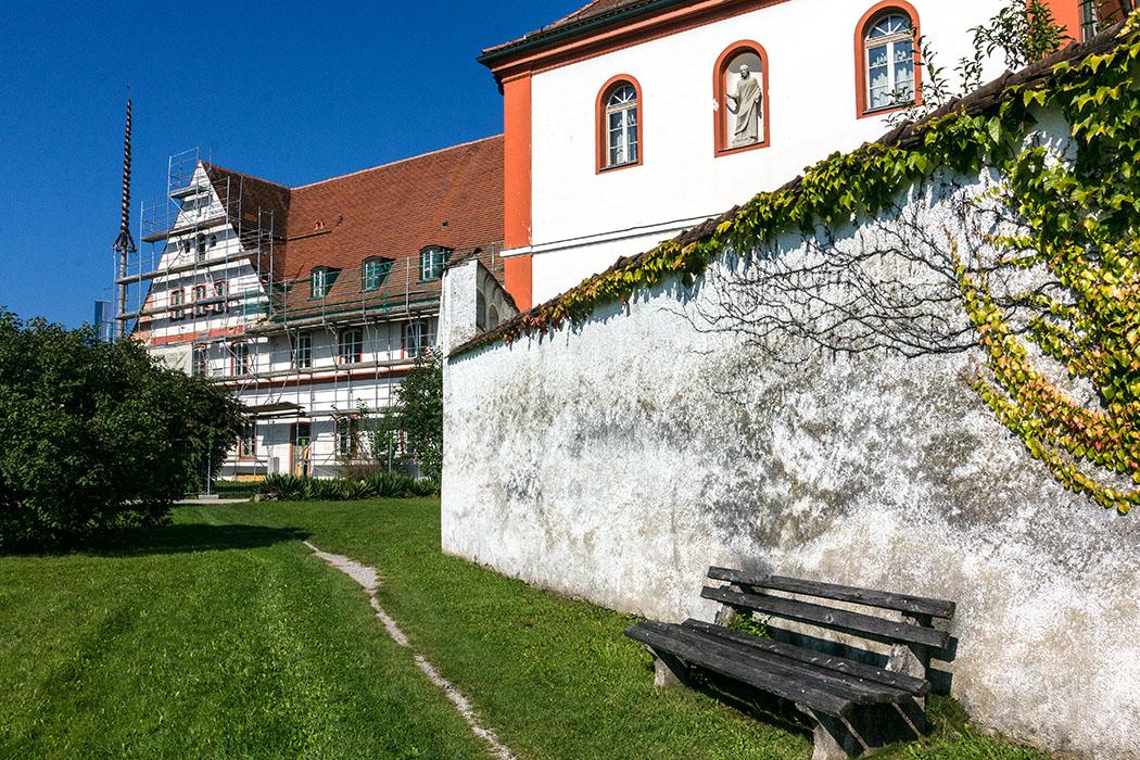 Auf dem Weg zur Klosterpforte von Beuerberg führt ein schmaler Weg an der efeubewachsenen Klostermauer entlang.