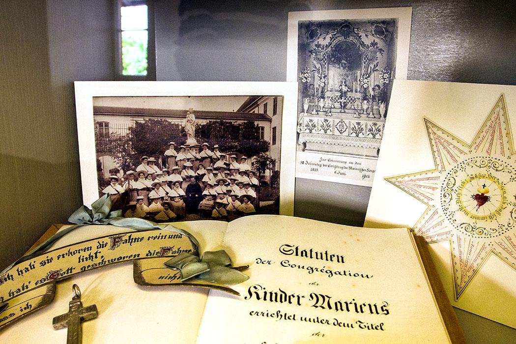 Sammelsurium aus der Klostergeschichte: Die Fotografie zeigt Schülerinnen des Pennsionats, eine Urkunde von 1905 erinnert an den 30 Jahrestag der Kongregation, das Buch beinhaltet die Statuten der Kinder Mariens ect.