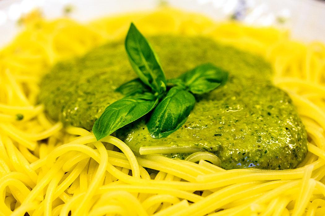 Die abgetropften Spaghetti in eine vorgewärmte Schüssel füllen und das Pesto alla genovese darübergeben.