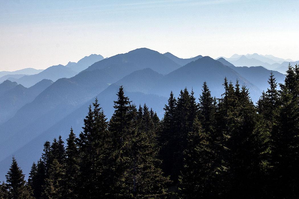 In der Mitte dominieren die Benediktenwand, Heimgarten und Herzogstand die Gebirgskulisse. Rechts hinten das Mangfallgebirge.