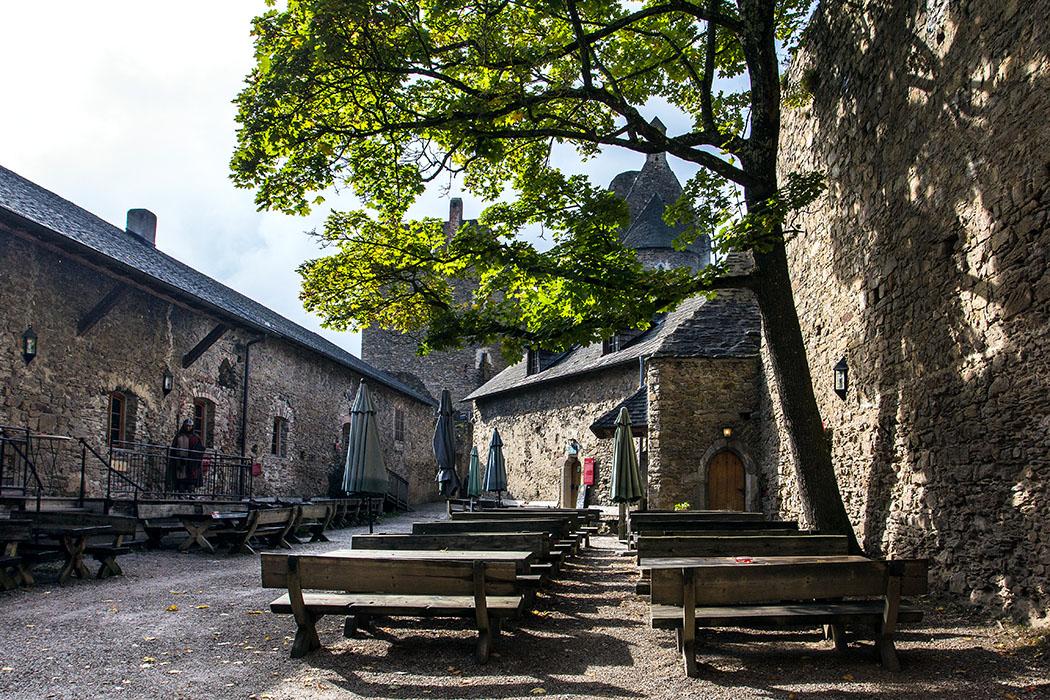 Der große innere Burghof bietet schattige Sitzplätze vor der empfehlenswerten Burgtaverne (rechts). Dahinter lugt die Burgkapelle zwischen den Blättern hindurch.