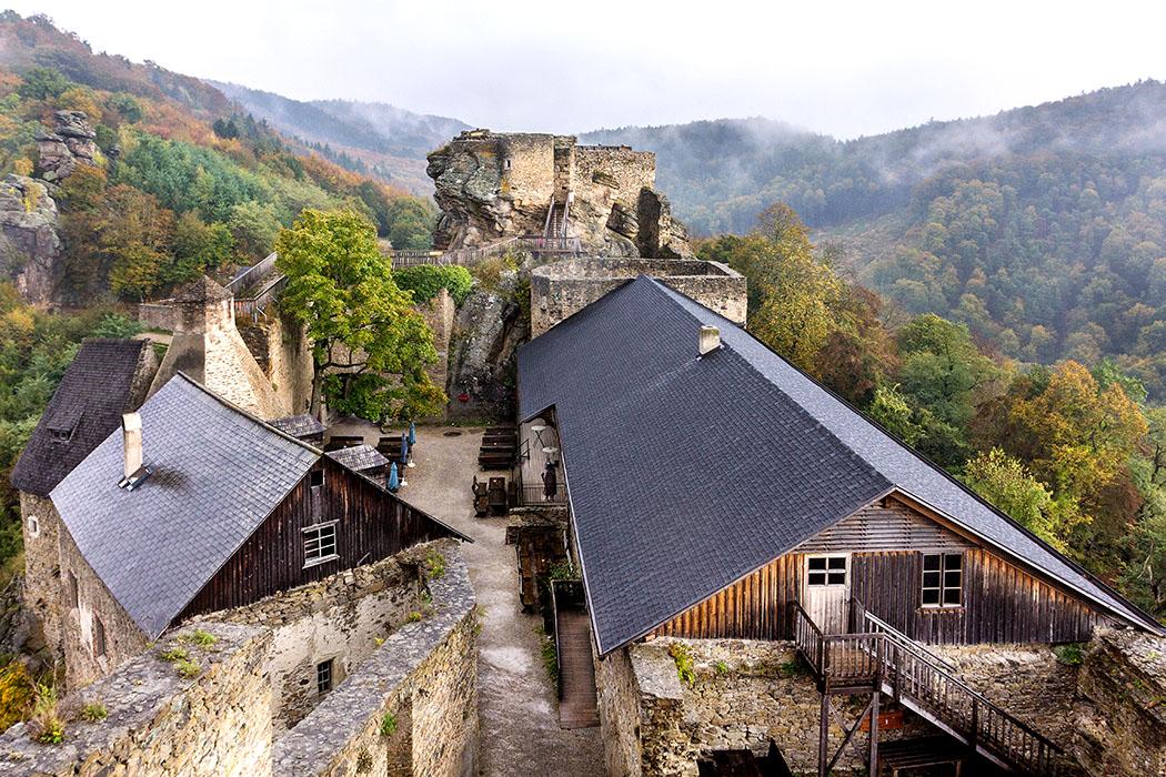 Blick von der Hochburg auf den großen Hof, links ist der pyramidenförmige große Kamin der Taverne erkennbar. Dahinter der Bürgel mit seinen Treppen und Aufbauten.