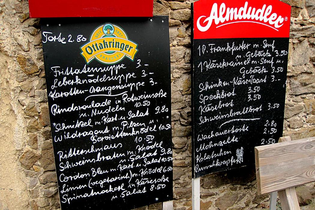 Vor der Taverne in der Burg Aggstein locken die Menütafeln mit Schnitzel, Ritterschmaus oder Wachauertorte.