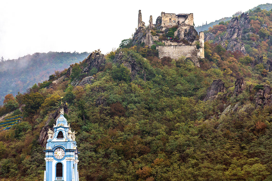 Auf steilen Felsen über der Donau thront die Burgruine von Dürnstein. Der blaue Turm der Stiftskirche bildet einen hübschen Kontrast vor dem herbstlich verfärbtem Wald.