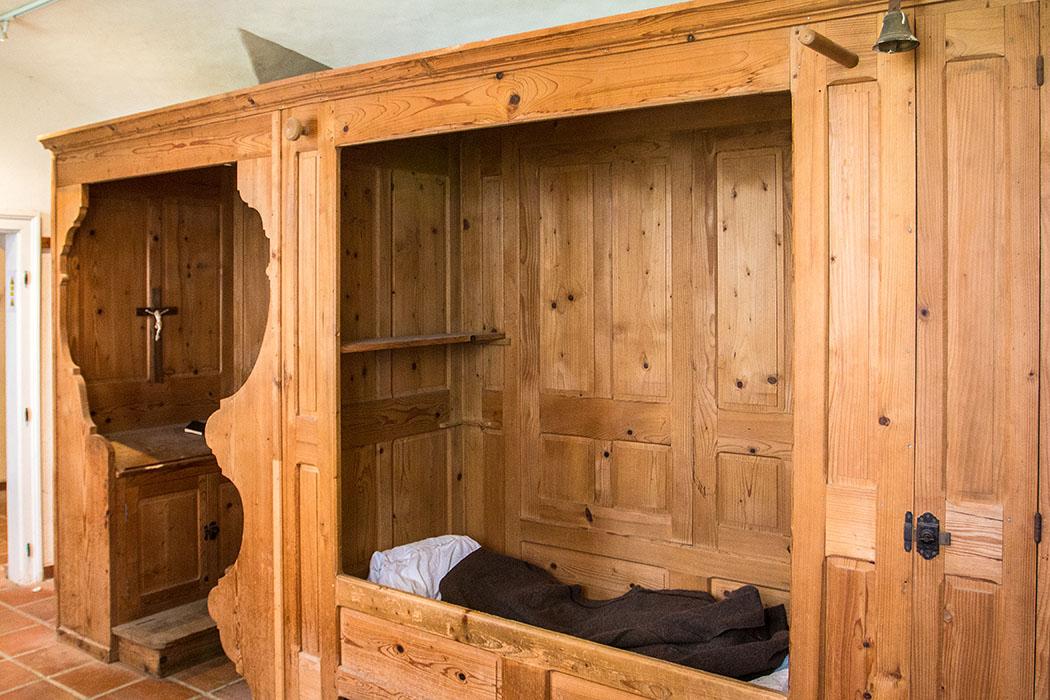 Das Bett eines Kartäusermönches mit angegliederter Sitzbank zum Beten.