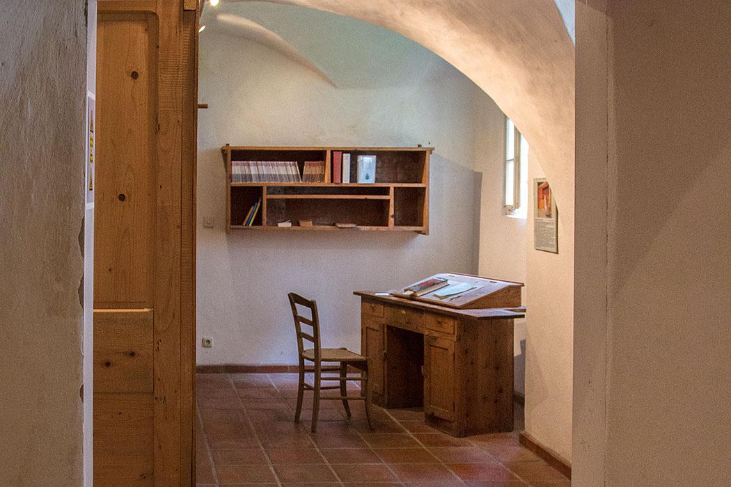 Eine Mönchszelle mit Schreibtisch, Stuhl und Bücherregal. Kartäuser führen ein strenges, kontemplatives Einsiedlerleben in einer Klostergemeinschaft.