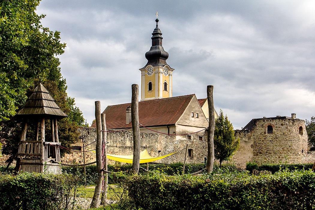 Die Westmauer und der U-Turm (Hufeisenturm) des einstigen Römerkastells Favianis in Mautern an der Donau. Dahinter lugt die Pfarrkirche St. Stephan über die Mauer. Der Spielplatz im Vordergrund mit seinem Holzturm passt perfekt ins Ensemble.