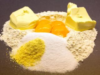 Die Zutaten für den Mürbeteig sind Mehl, Butter (oder Margarine), Zucker, Zitronenschale und Eigelb.