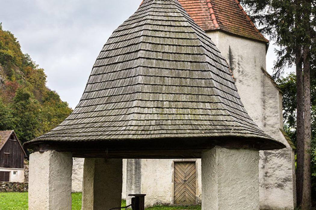 Neben der Kirche befindet sich das Brunnenbecken, das von einer Schindelhaube überdacht ist. Die Forscher vermuten, dass sich hier einst ein keltisches Quellheiligtum befand, das später in eine christliche Kirche verwandelt wurde.