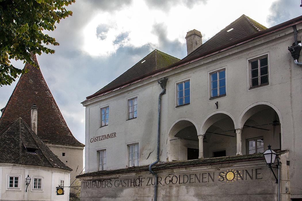 """Das Eckhaus """"Gasthof zur goldenen Sonne"""" am Schürerplatz hat einen Baukern aus dem 15./16. Jahrhundert. Der hohe Sockel ist zugleich das Erdgeschoß. Darüber liegen zwei Stockwerke. Zum Platz hin sind Arkaden mit Pfeilern zu sehen, die Räume im Inneren sind Tonnen- und Kreuzgratgewölben aufgeführt."""