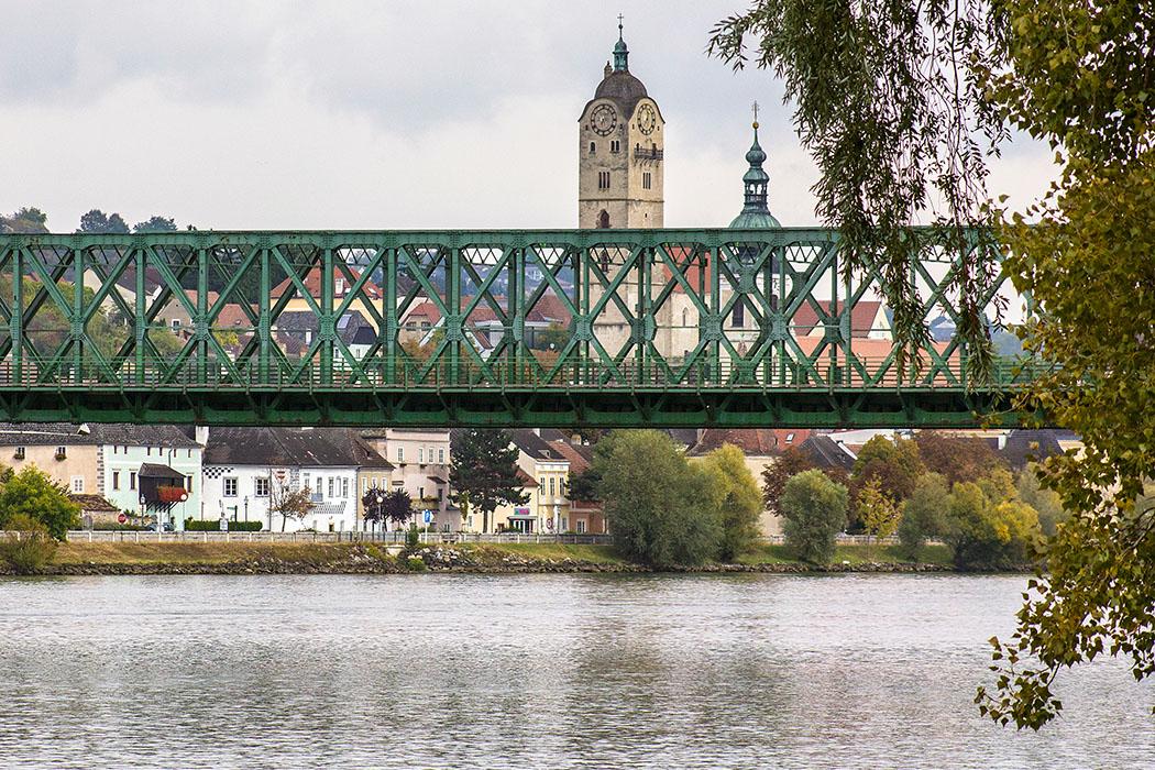 Blick von Mautern an der Donau hinüber nach Stein mit den markanten Kirchtürmen der Frauenbergkirche und der Pfarrkirche Hl. Nikolaus. Im Vordergrund die Mauterner Brücke, eine Stahlfachwerksbrücke von 1895.