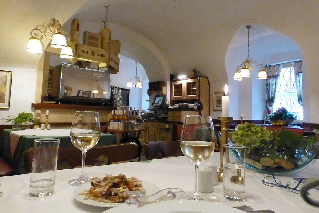 Blick in die Gaststube vom Kirchenwirt. Unseren Tisch schmücken der hervoragende Weißwein ... und die Reste vom Backhendl ...